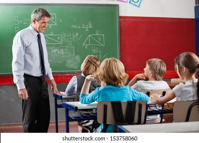Side view of mature male teacher looking at students sitting in classroom