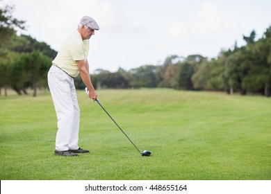 Side view of mature man playing golf