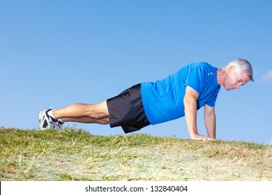 Side view of a mature man in sportswear doing push ups on ground against clear sky. Horizontal shot.