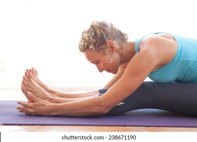 Side view of a mature professional woman exercising and stretching her body doing flexibility exercises and bending her back, sitting on a yoga mat indoors. Senior woman fit and healthy lifestyle.