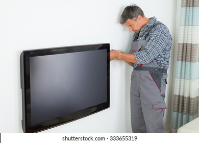 Side view of mature technician installing television at home