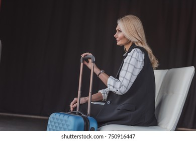 side view of mature woman with suitcase in waiting room