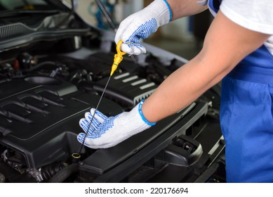 Side view of mechanic checking motor oil in a car with open hood