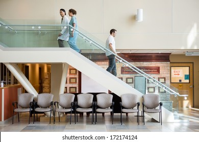 Side view of medical team and man using staircase in hospital
