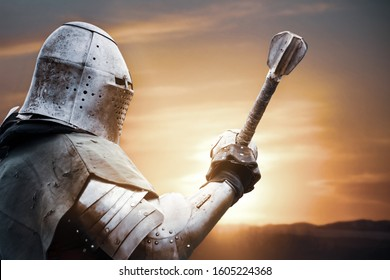 Side view of medieval knight in iron armor posing and raising big sword. Close up portrait of brave man standing outdoors while sun raising in sky. Concept of warrior, middle ages.