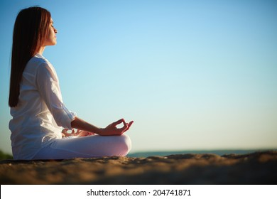 Side view of meditating woman sitting in pose of lotus against blue sky outdoors