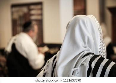 Side view of men with prayer shawls praying the Jewish prayers
