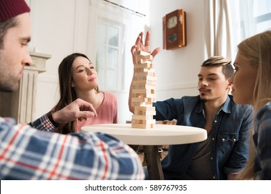 side view of men and women playing jenga game at home