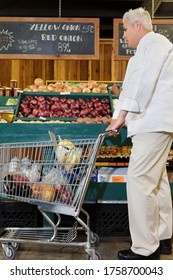 Side view of mid adult chef with shopping cart in market