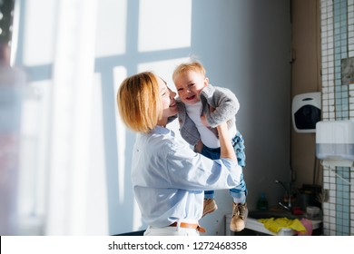Side view of mid adult european mom lifting happy toddler son into air indoors. Bright day. Window frame shadow on the wall.
