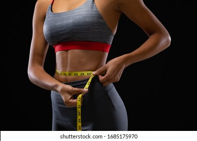 Side view mid section of a fit mixed race woman wearing sportswear and measuring her waist with measuring tape on a black background.