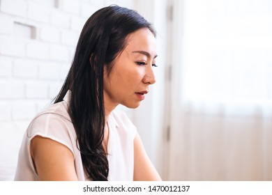 Side view of middle aged beautiful woman sitting upset and thinking about problems indoors