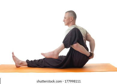 Side view of middle aged man doing yoga in studio