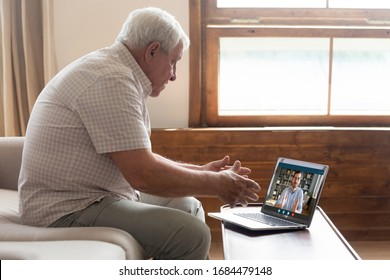 Side view middle aged mature older man sitting on sofa, looking at computer screen, holding video call listening grown up handsome son, explaining how important stay at home during virus outbreak.