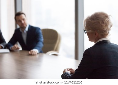 Side view middle ages businesswoman sitting in office at meeting. Director, boss or workers team sitting on a background. Negotiations, passing interview, hr, hiring, recruiting and retirement concept