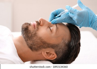 Side view of middle-aged man getting beauty injection in nose at aesthetic clinic. Plastic surgeon injecting anti-aging filler in handsome bearded man nose, having plastic correction, closeup - Shutterstock ID 1892134360