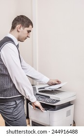 Side view midsection Portrait of young adult businessman using photocopy machine in office Business man white collar holding paper document against texture wallpaper background Empty space