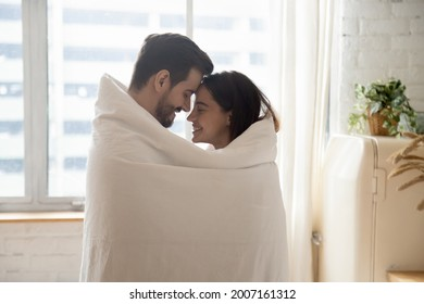 Side view millennial beautiful romantic couple awakened together wrapped in blanket standing together in kitchen, enamoured spouses embracing smiling touch foreheads enjoy moment of tender and love