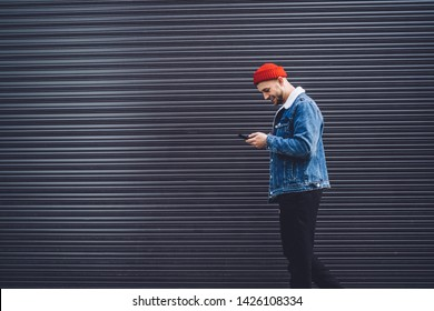Side view of millennial man in stylish denim outfit walking near advertising city wall and writing online message via modern mobile phone, trendy dressed male blogger networking via smartphone