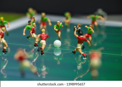 Side view of miniature toys figurines football (soccer) players on a computer electronic pad.