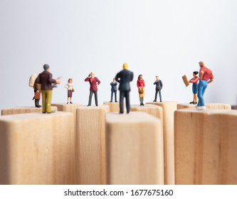 Side view of miniature toys standing on wooden block - social distancing, anti-social or team work concept.
