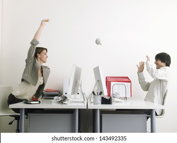 Side view of mischievous businesswoman throwing paper ball on male executive over desks