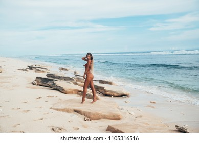 Side view of a model posing against a white desert beach and blue water. A slim, suntanned girl walks along the white sand in a fashionable sexy swimsuit.