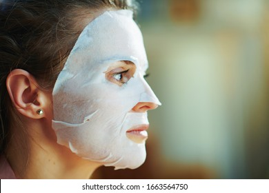 Side view of modern 40 years old woman in pajamas with white sheet facial mask on face in the modern living room in sunny winter day.