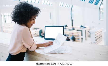 Side view of modern African American female reading paper documents while standing at counter with laptop with white blank screen in modern light library