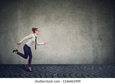 Side view of modern formal business woman running forward under time pressure willing to manage professional competition against gray wall