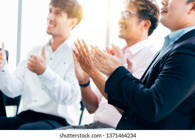 Side view of modern formal men in suits sitting in sunny office and applauding while having business presentation