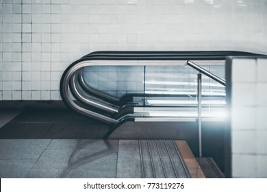 Side view of modern glass and chrome escalator in urban underground with white tiles in background; city contemporary moving staircase with stairs next to it following down into subway