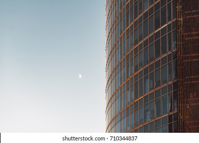 "Side view of modern skyscraper teal and orange glassy facade with blue sky and moon on other side, offices overlooked behind windows, ""Moscow City"" business skyscrapers group, Russia"
