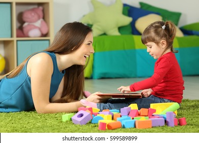 Side view of a mom and toddler playing with a book sitting on a carpet in the bedroom at home