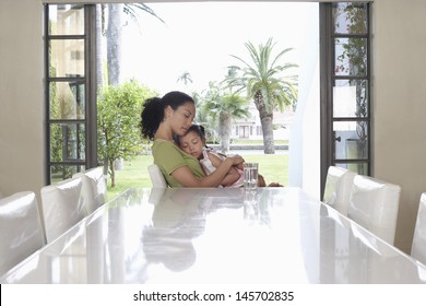 Side view of mother and daughter sitting with eyes closed at dining table