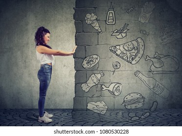 Side view of a motivated young woman resisting temptation of eating fast foot and choosing better diet.