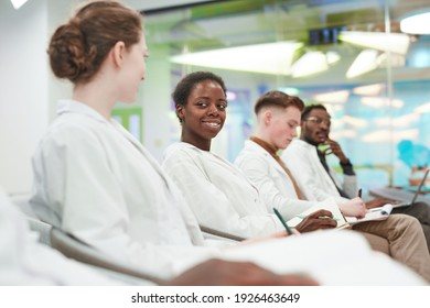 Side view at multi ethnic group of young people wearing lab coats while sitting in row in audience and listening to lecture on medicine