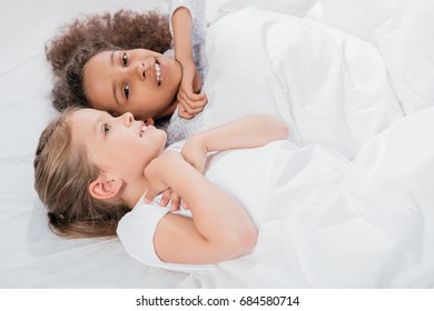 side view of multicultural adorable girls resting in bed at home