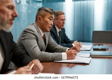 Side view of multicultural business team in formal wear having a meeting in the modern office. Business people working together. Business concept