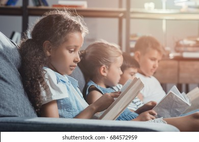 side view of multicultural group of children reading books while sitting on sofa at home together