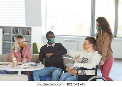 Seitenansicht einer multiethnischen Gruppe von Studierenden, die während ihres Studiums in der Universitätsbibliothek Masken tragen, mit jungen Männern, die Rollstuhl im Vordergrund benutzen, Kopienraum