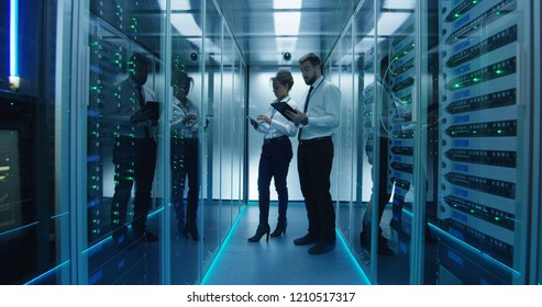 Side view of multiethnic man and woman with tablets coworking in data center server room checking hardware