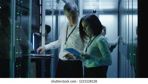 Side view of multiethnic man and woman with tablet diagnosing server hardware opening glass door of rack in data center corridor