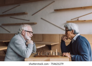 side view of multiethnic senior men playing chess
