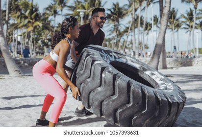 Side view of multiracial athletic man and woman pushing heavy car tyre on sand with park on background.