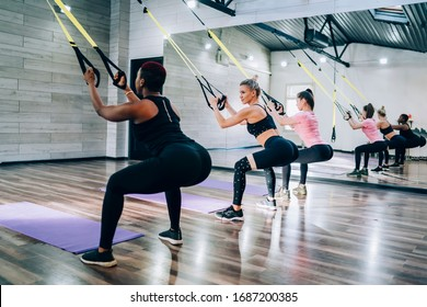 Side view of multiracial group of young athletic ladies wearing sportswear working out by doing suspension training in fitness studio