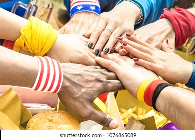 Side view of multiracial hands of football supporter friend sharing street food - Friendship concept with soccer fan enjoying food together - People eating at party bar pub after sport match event