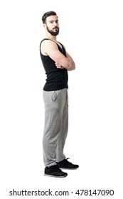 Side view of muscular athlete in tank top with crossed arms looking at camera. Toned desaturated full body length portrait isolated on white studio background.