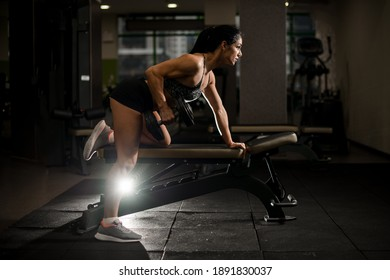 Side view of muscular athletic brunette woman who trains in gym with dumbbell in her hand on simulator.
