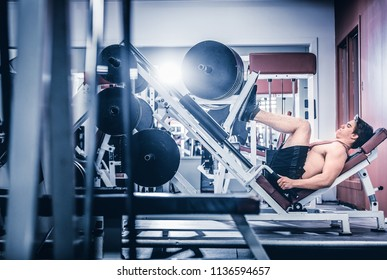 Side view of muscular bodybuilder training in gym doing leg pressing with big weight.